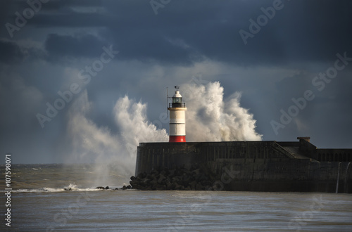Foto op Aluminium Nachtblauw Large sea waves crashing over lighthouse during storm with beaut