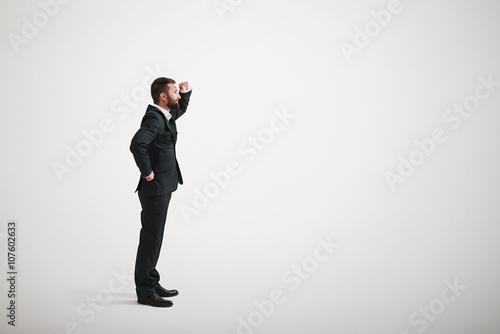 Obraz na plátně A bearded man in a black business suit looks into the distance