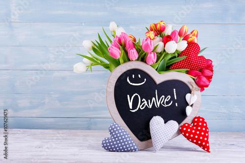 Muttertag - Bunter Blumenstrauß, Herzen und Tafel mit Aufschrift DANKE vor Holzhintergrund