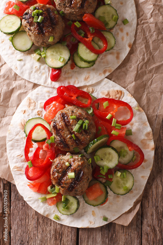 Grilled meat balls with fresh vegetables on a flat bread close up. Vertical top view