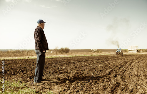 фотография  farmer looking at tractor plowing ground at spring season