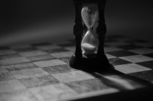 Wooden Hourglass On An Empty Chess Board (as The End Of Game Concept), In Black And White, Shallow DOF With Selective Focus