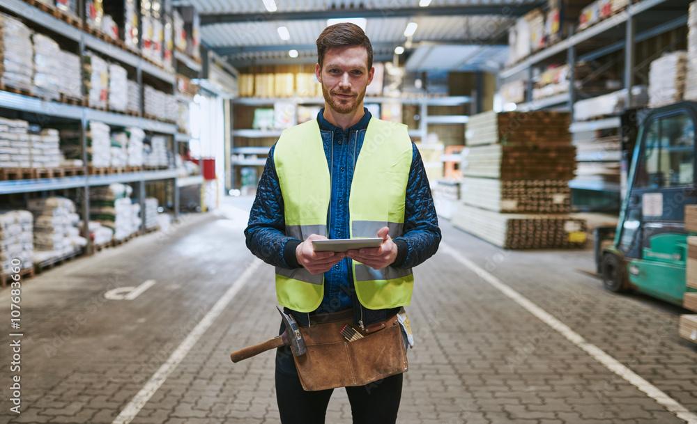 Fototapeta Young handyman or builder in a warehouse