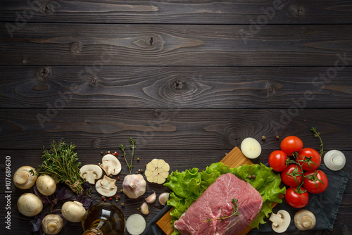 Door stickers Meat raw meat with ingredients on a wooden background