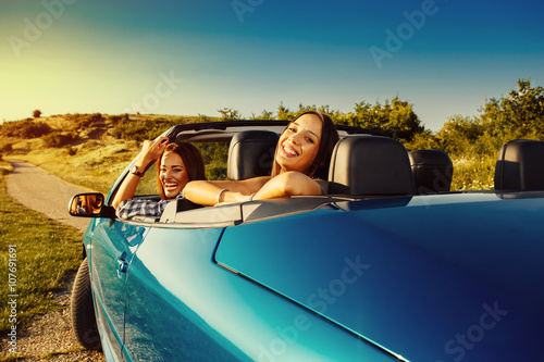 Two attractive young woman having fun in a convertible Fototapeta