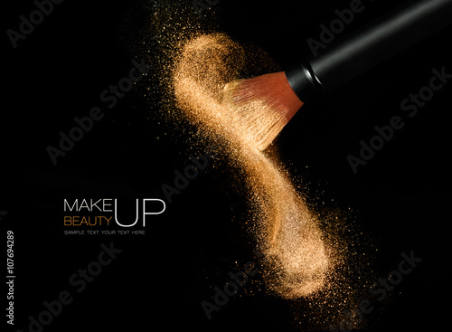 Fotografie, Obraz  Cosmetics brush with glowing face powder. Dust explosion