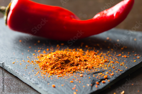 Closeup of dry ground chile on stone board with fresh red  chili on background Fototapet