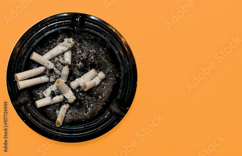 Dirty round dirty ashtray with cigarette butts and stubs extinguished Canvas Print