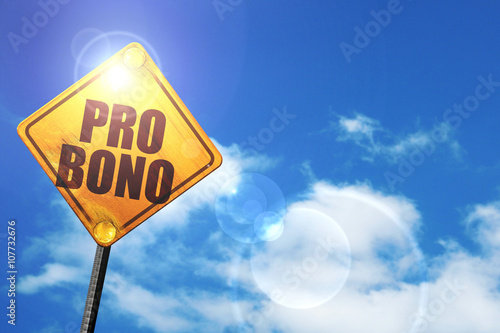 Yellow road sign with a blue sky and white clouds: pro bono Wallpaper Mural