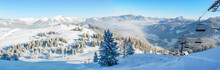 Alpine Ski Slope Mountain Winter Panorama With Ski Lift,skiers And Snow Covered Forest.