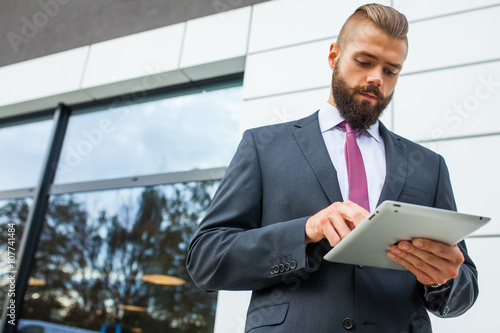 Fototapety, obrazy: Young bearded businessman writting business e-mail using his tab