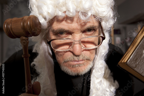 Fotografija  Old male judge in a courtroom striking the gavel