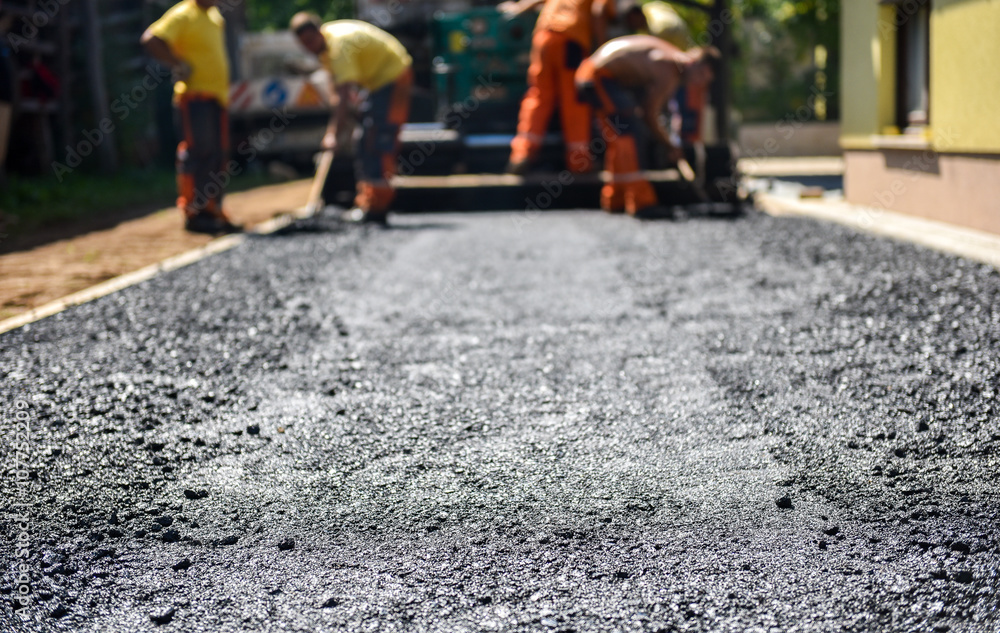 Fototapeta Team of Workers making and constructing asphalt road constructio
