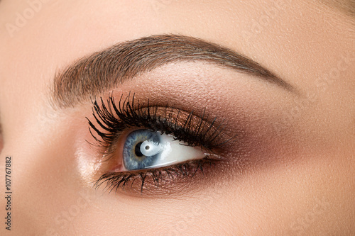 Fotografering  Close-up of woman eye with beautiful brown smokey eyes makeup