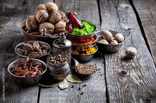 Fotografering Spices and nuts at wooden table