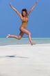 femme heureuse sautant sur une plage de sable blanc