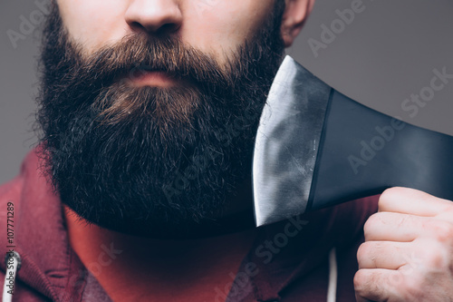 Fotografie, Obraz  Close up of beard Confident young bearded man carrying a big axe on shoulder and