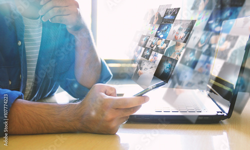 Fotografía  Man Sitting in front of laptop and holding smartphone