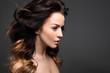 Loki, włosy pełne objętości. Portret pięknej kobiety na czarnym tle.
