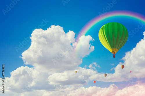 Poster Montgolfière / Dirigeable colorful hot air balloons and rainbow with cloudy blue sky background