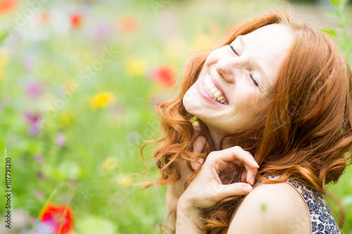 schöne lachende Frau in der Blumenwiese Canvas-taulu