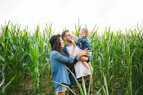 Fényképezés  Young hipster father mother holding cute baby in corn field