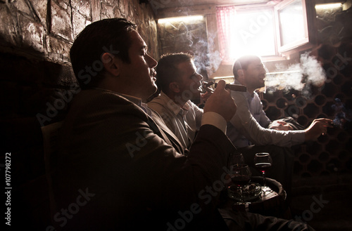 Fototapeta  Three businessmen sitting in the wine cellar drinking wine and smoke cigar, resting after a hard day at work