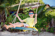 Cute boy having fun swinging at tropical island beach