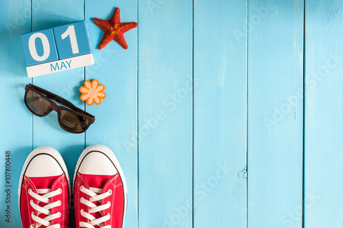 May 1st. Image of may 1 wooden color calendar on blue background. Spring day, empty space for text. International Workers' Day