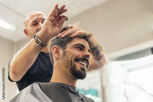 mata magnetyczna Hairstylist making men's haircut to an attractive man.