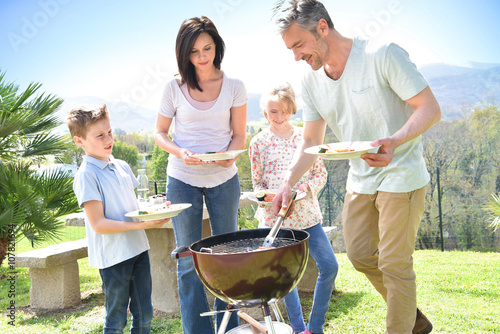 Papiers peints Grill, Barbecue Family having barbecue lunch in garden