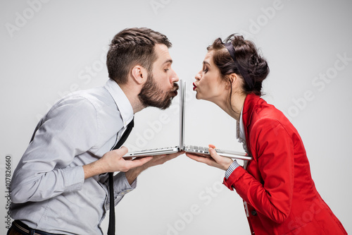 Photo The young businessman and businesswoman with laptops kissing screens on gray bac