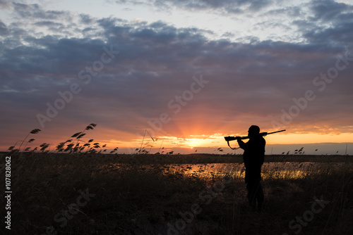 Deurstickers Jacht Silhouette of the hunter with the shot gun on a sunset background