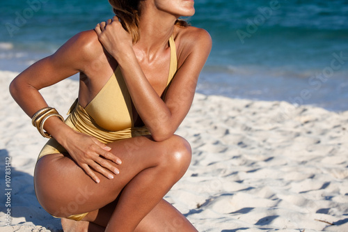Midsection of woman in golden swimsuit kneeling on beach