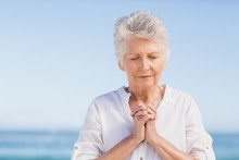 Senior Woman Praying On The Beach