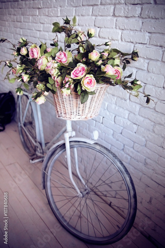 Foto op Plexiglas Fiets Old bicycle and flowers close to the white brick wall