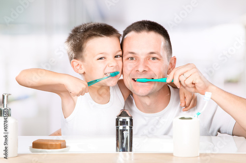 Fotografia  smiling child brushes his teeth with dad in the bathroom
