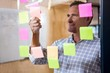 Man looking at sticky notes on window