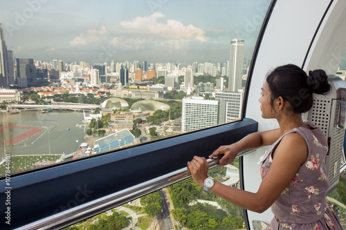 woman looks at the city from cabine of Ferris wheel Poster