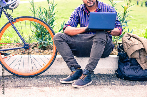 Fotografia Indian man with laptop and sport bike sitting in city park - University asian st