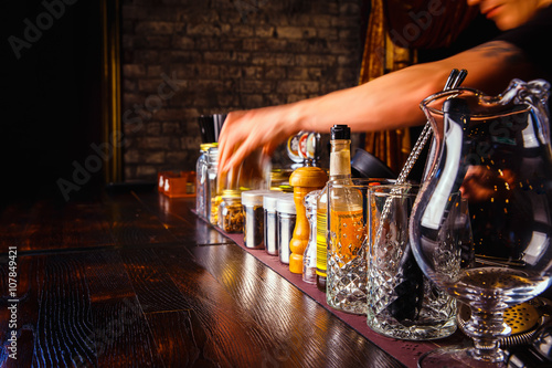 Bartender works with tools on bar