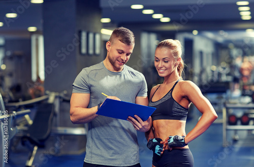 Obraz na płótnie smiling young woman with personal trainer in gym