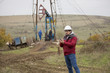 Oil worker in uniform and helmet, with mobile phone.