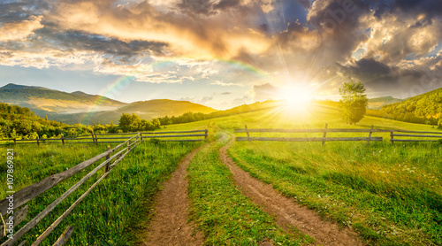 Poster Miel road and wooden fence on hillside at sunset