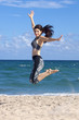 Pretty woman jumping with excitement on a beach with ocean in the background