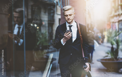 Fotografia  Serious professional lawyer using smart phone while walking on the street during