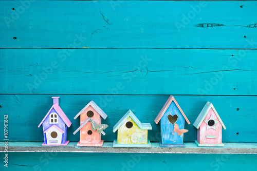 Canvas Print Row of colorful spring birdhouses with teal blue background
