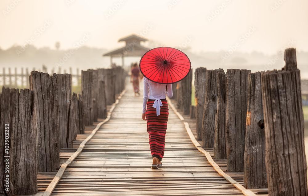 Fototapeta Burmese woman holding traditional red umbrella and walking on U Bein Bridge