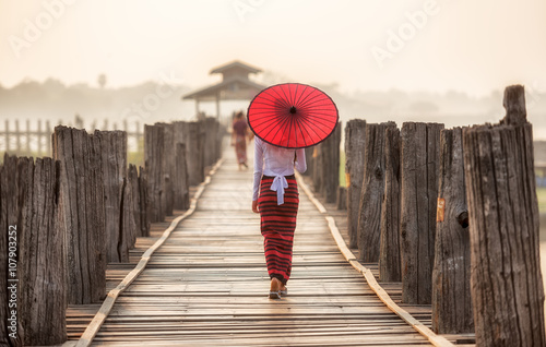 Burmese woman holding traditional red umbrella and walking on U Bein Bridge Canvas Print
