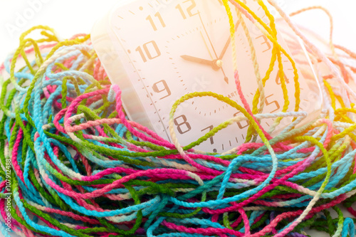 Fotografie, Obraz  Busy time, clock is wrap with tangled yarn, time concept